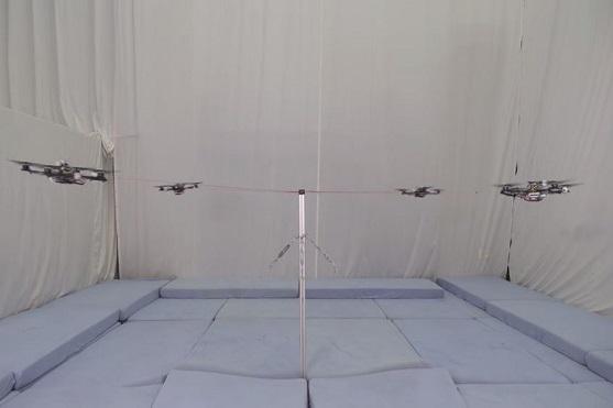 Kvadrokoptéry přivázané lanem k tyči ve speciálním prostoru zvaném Flying Machine Arena | Zdroj: video